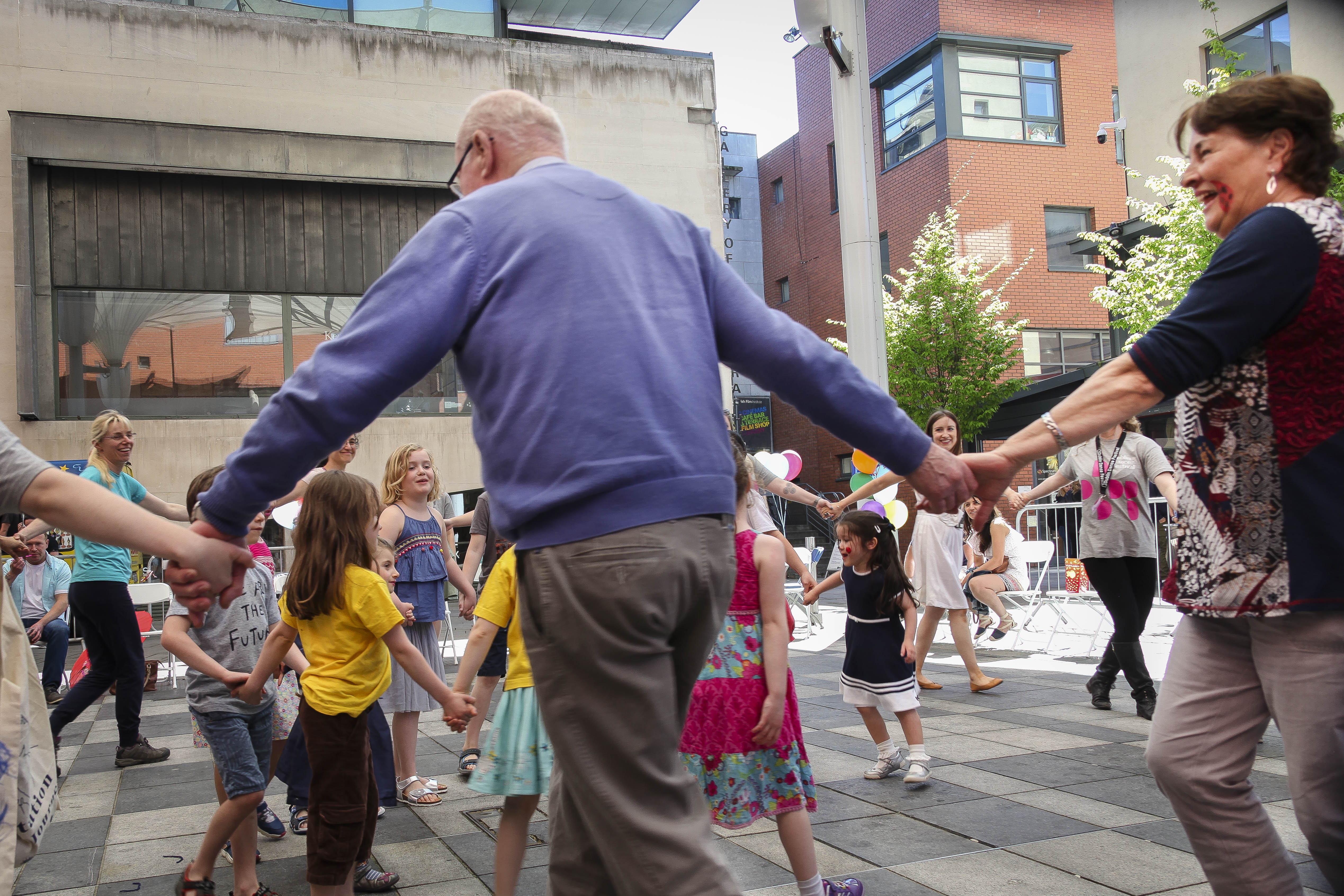 Older people and younger people dancing in Meeting House Square in Temple Bar, as part of a 2018 Bealtaine Festival event called a Life of Play.